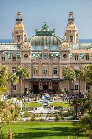 Monaco, Monte-Carlo, 02 October 2019: The main sight of the principality casino surrounded with the green trees, the updated facade, through the fountain, hotel the Paris, sunny day