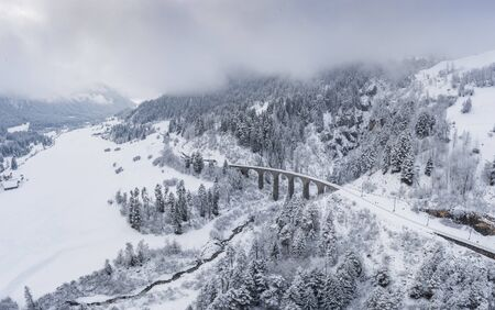 Aerial View of the Landwasser Viaduct with Railway without famous train at winter, landmark of Switzerland, snowing, river and mountains