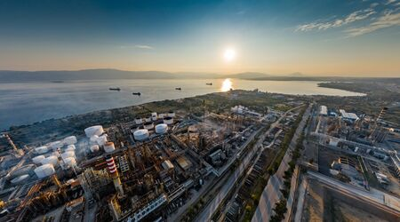 Aerial view of Chemical plant at sunset, oil refining, smoke, pipes, ecology pollution, air infection, coast of sea in Greece, Oil tankers expect loading