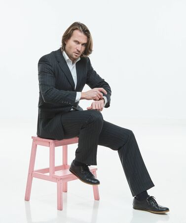 The handsome men in black suit sits on a pink chair, brutal man with long hairs, white shirt, business man, very stylish, looking in the camera