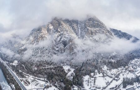 Aerial view of mountain with boundary tower, forest underneath fog, slopes with snow covered in Switzerland, cloudy atmosphere, beautiful conditions