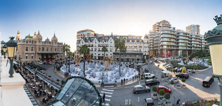 Monaco, Monte-Carlo, 25 December 2019: Panorama of the square Casino Monte-Carlo at sunset, white Christmas trees, hotel the Paris, sunny day, Christmas decoration, tourists, fountain, new apartments Éditoriale