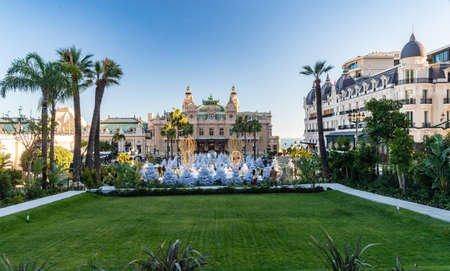 Monaco, Monte-Carlo, 25 December 2019: The square Casino Monte-Carlo at sunset, white Christmas trees, hotel the Paris, sunny day, Christmas decoration, tourists, fountain, new apartments, green lawn Éditoriale