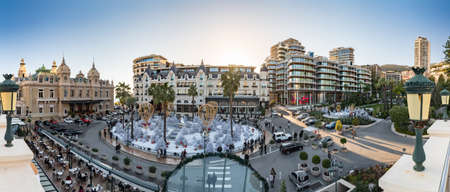 Monaco, Monte-Carlo, 25 December 2019: Panorama of the square Casino Monte-Carlo at sunset, white Christmas trees, hotel the Paris, sunny day, Christmas decoration, tourists, fountain, new apartments