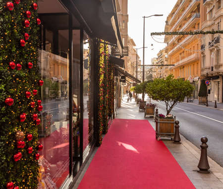 Monaco, Monte Carlo, 25 December 2019: The street in Monaco for Christmas at sunset, the sunshine, the decorated facades of shops for a holiday, a red path before an entrance to shop, without people