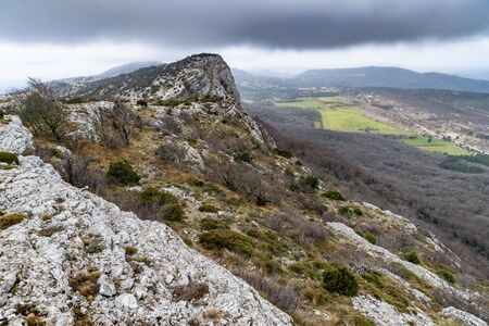 The mountain over grotto of Mary Magdalene at cloudy weather, clouds over a valley, a dry grass