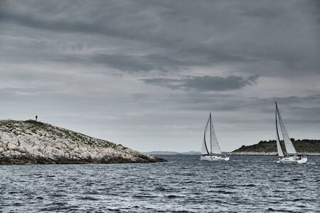 Seascape of the sailboat in the foreground, the men on the island is on background, Croatia