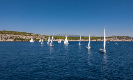 Aerial shot of the yacht race, a sailing regatta, intense competition, a lot of white sails, island is on background, top travel destination, vacation in Croatia, idyllic landscape