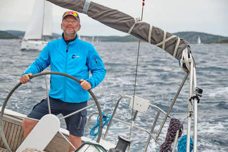 Croatia, Adriatic Sea, 19 September 2019: The brutal captain of the boat is at a steering wheel, jacket of blue color, sailboat compete in a sail regatta