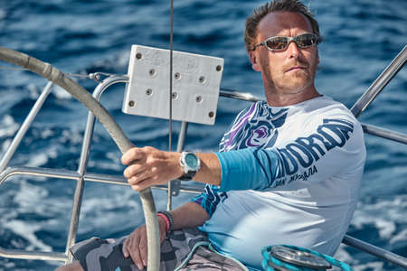 Croatia, Adriatic Sea, 17 September 2019: The brutal captain of the boat is at a steering wheel, sailboat compete in a sail regatta, a race, island with lighthouse are on background Redactioneel