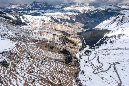 Aerial view of twisting road in mountains of Italy, Dolomites, is serpentine among the snow-covered hills, is famous place among skiers and fans to understand a known by sports cars, mountains peak