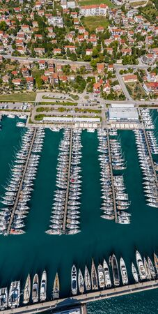 Croatia, marina Kastela, Drone view point on moored in an equal row sailboats, participant of a sailing regatta, piers, a lot of boats, mountains is on background, piers