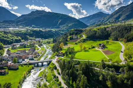 Aerial view of valley Cares, Trentino, green slopes of the mountains of Italy, huge clouds over a valley, roof tops of houses, Dolomites on background, bridges, river and roads, spring colors
