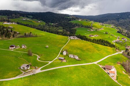 Aerial view of improbable green meadows of Italian Alps, green slopes of the mountains, huge clouds over a valley, roof tops of houses, Dolomites on background, sunshines through clouds Foto de archivo