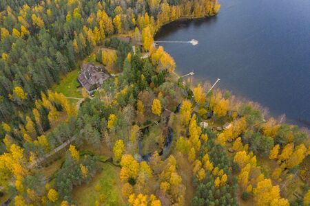 Drone view point of rural area in Autumn with lake Boroye, The big wooden house in forest, Piers on the lake, Valday national park, Russia, panoramic image, golden trees, Wooden lodges, cloudy weather