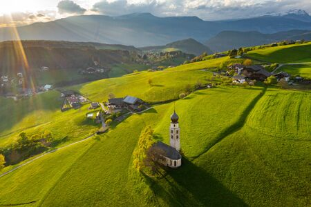 Aerial view of picturesque valley with chapel in Bolzano at sunset, Trentino, amazing green meadows of the mountains of Italy, roof tops of houses, Dolomites on background, drone flies around chapel Foto de archivo