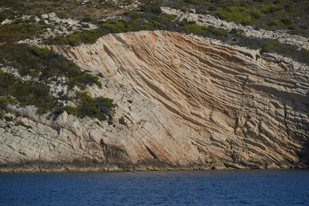 Beautiful high cliff with caves and hanging rocks of a mountain in Adriatic sea, a crevice, colorful