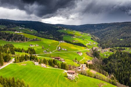 Aerial view of improbable green meadows of Italian Alps, green slopes of the mountains, Bolzano, huge clouds over a valley, roof tops of houses, Dolomites on background, sunshines through clouds