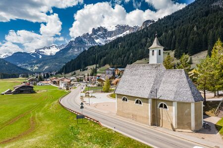 Aerial view of valley with Chalet, green slopes of the mountains of Italy, Trentino, Fontanazzo, huge clouds over a valley, roofs of houses of settlements, green meadows, Dolomites on background,