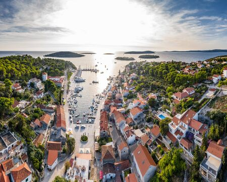 Croatia, Maslinica, Drone view point on moored in an equal row sailboats at sunset, participant of a sailing regatta, people have a rest after racing day, azure water, pier