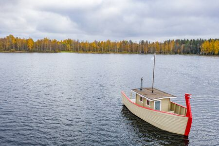 Drone view point of Wooden boat bath on a lake, water area in Autumn with lake Boroye, Valday national park, Russia, panoramic image, golden trees, Wooden lodges, cloudy weather Foto de archivo
