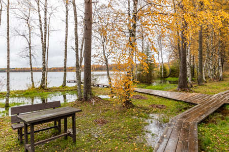 The Long pier on the lake, Terrace at the lake, the Autumn at the lake Boroye, Boats at a pier, Valday national park, Russia, panoramic image, golden trees, Wooden lodges, cloudy weather Foto de archivo
