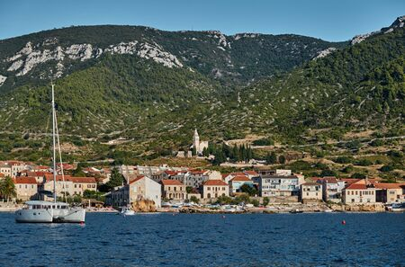 Seascape of city Komiza - the one of numerous port towns in Croatia, Catamaran in the foreground, orange roofs of houses, a cathedral St.Nicholas, Picturesque slopes of mountains