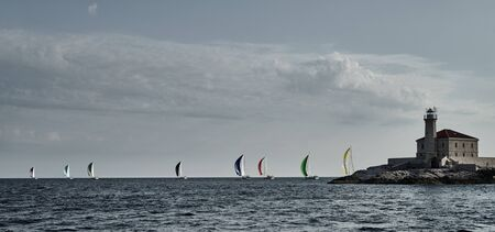 Sailboats compete in a sail regatta at sunset, Boats bend around the island with a beacon, a race, multicolored spinnakers, number of boat is on aft boats, island is on background