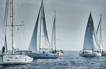 Croatia, Mediterranean Sea, 18 September 2019: Sailboats compete in a sailing regatta, the team turns off the boat, reflection is on water, white sails, boat number aft boats, Strained competition Sajtókép