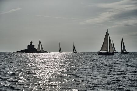 Sailboats compete in a sail regatta at sunset, Boats bend around the island with a beacon, a race, multicolored spinnakers, number of boat is on aft boats, island is on background, clear weather