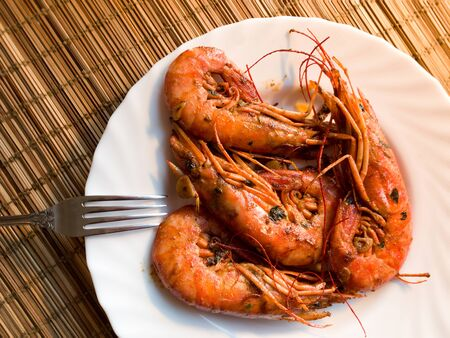A fried lobster on a white plate, a straw lining under plate, fork, garlic, close up Reklamní fotografie