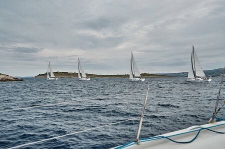 Croatia, Adriatic Sea, 19 September 2019: The race of sailboats, the team sits on the edge of a boat board, bright colors, view of participants of race from other boat through ropes