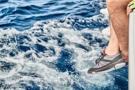 Feet of the sailor hang down from a boat board over azure water, footwear for yacht, splashes of water, sun patches of light on water, sailing, sunny weather, sun reflections