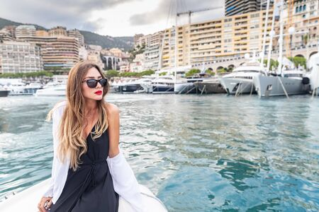The elegant girl dressed in an evening dress of black color and sunglasses on the boat carry to the big yacht, gorgeous woman, sexual red lips, Decollete, Monaco, Monte-Carlo Stock Photo