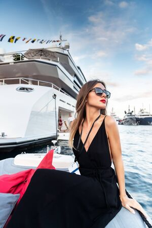 The elegant girl dressed in an evening dress of black color and sunglasses on the boat carry to the big yacht, gorgeous woman, sexual red lips, Decollete, Monaco, Monte-Carlo Foto de archivo