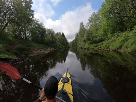 The men in a cap floats on a kayak on the forest quiet river, the beautiful landscape, a changeable weather, actively rows with an oar, beautiful reflection