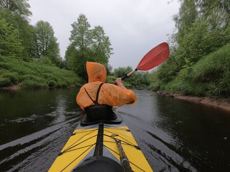 The men in a raincoat of orange color floats on a kayak on the forest quiet river, the beautiful landscape, a rainy weather, actively rows with an oar, beautiful reflection
