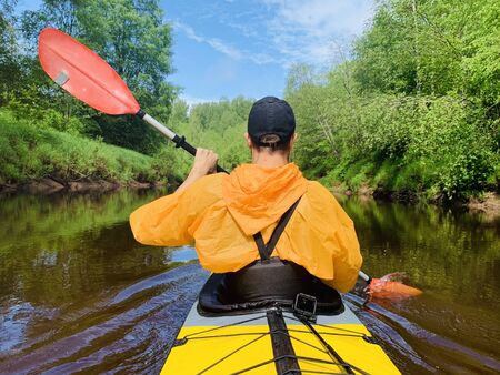 The men in a cap and raincoat of orange color floats on a kayak on the forest quiet river, the beautiful landscape, a changeable weather, actively rows with an oar, beautiful reflection
