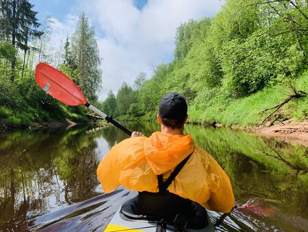 The men in a cap and raincoat of orange color floats on a kayak on the forest quiet river, the beautiful landscape, a changeable weather, actively rows with an oar