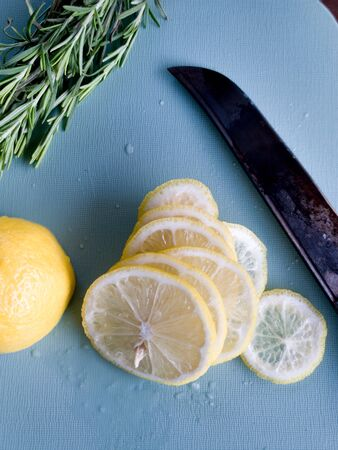 Slices of a lemon and branch of a rosemary lie on a plastic cutting board of blue color, a knife blade. High quality photo