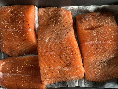 Some pieces of fillet of raw red fish with spices lie on a baking sheet before smoking, black pepper and salt, salmon