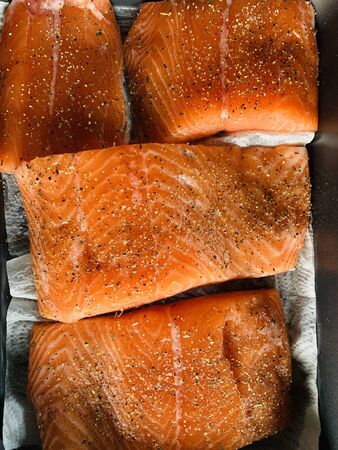 Some pieces of fillet of red fish with spices lie on a baking sheet before smoking on a grill, black pepper and salt, salmon. High quality photo