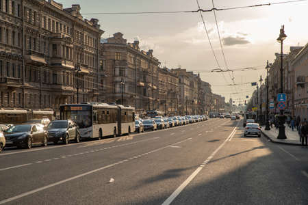 Russia, St.Petersburg, 09 June 2020: The architecture of Nevsky Prospect at sunset during pandemic of virus Covid-19, long shadows, traffic, dust, slow motion. High quality 4k footage