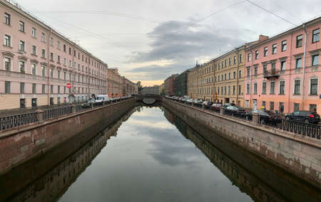 Russia, St.Petersburg, 09 June 2020: Griboyedov Canal at sunset, specular reflection in water, architecture of St. Petersburg, the bridge through the river Editorial