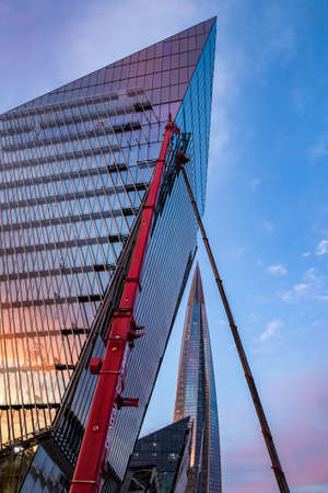Russia, St.Petersburg, 03 July 2020: The color image of skyscraper Lakhta center at sunset, Reflection of the sunset sky in a glass facade of the building, Completion of construction, Huge crane Editorial