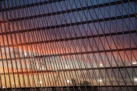 Reflection of the sunset sky in a glass facade of the building, skyscraper at sunset, pink sky Foto de archivo