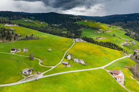 Aerial view of improbable green meadows of Italian Alps, green slopes of the mountains, huge clouds over a valley, roof tops of houses, Dolomites on background, sunshines through clouds