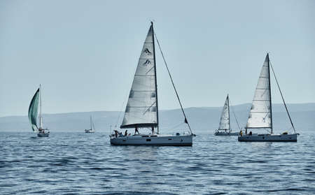 Croatia, Adriatic Sea, 15 September 2019: The race of sailboats, a regatta, reflection of sails on water, Intense competition, bright colors, island with windmills are on background Éditoriale