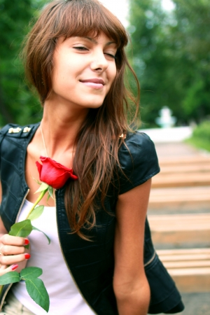 a girl holding a rose Bud photo
