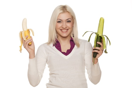 beautiful girl hesitating about bananas and cucumbers on white background Stock Photo - 17537585